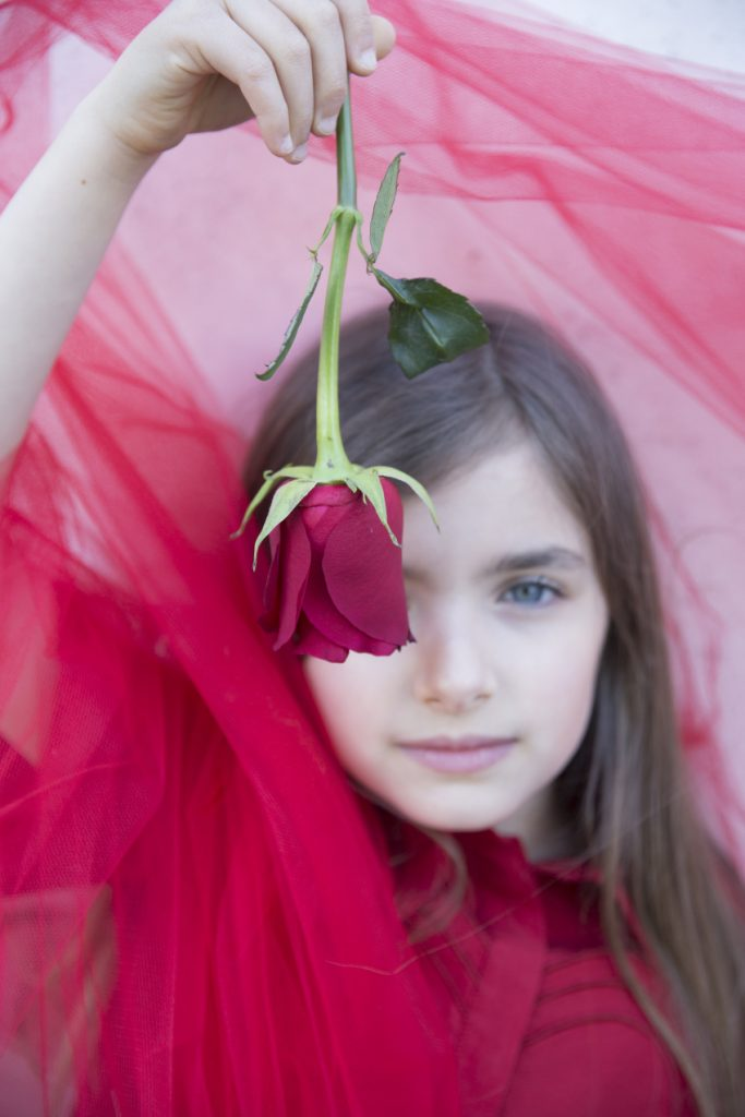 Giulia is the red rose and wears a dress from Simonetta